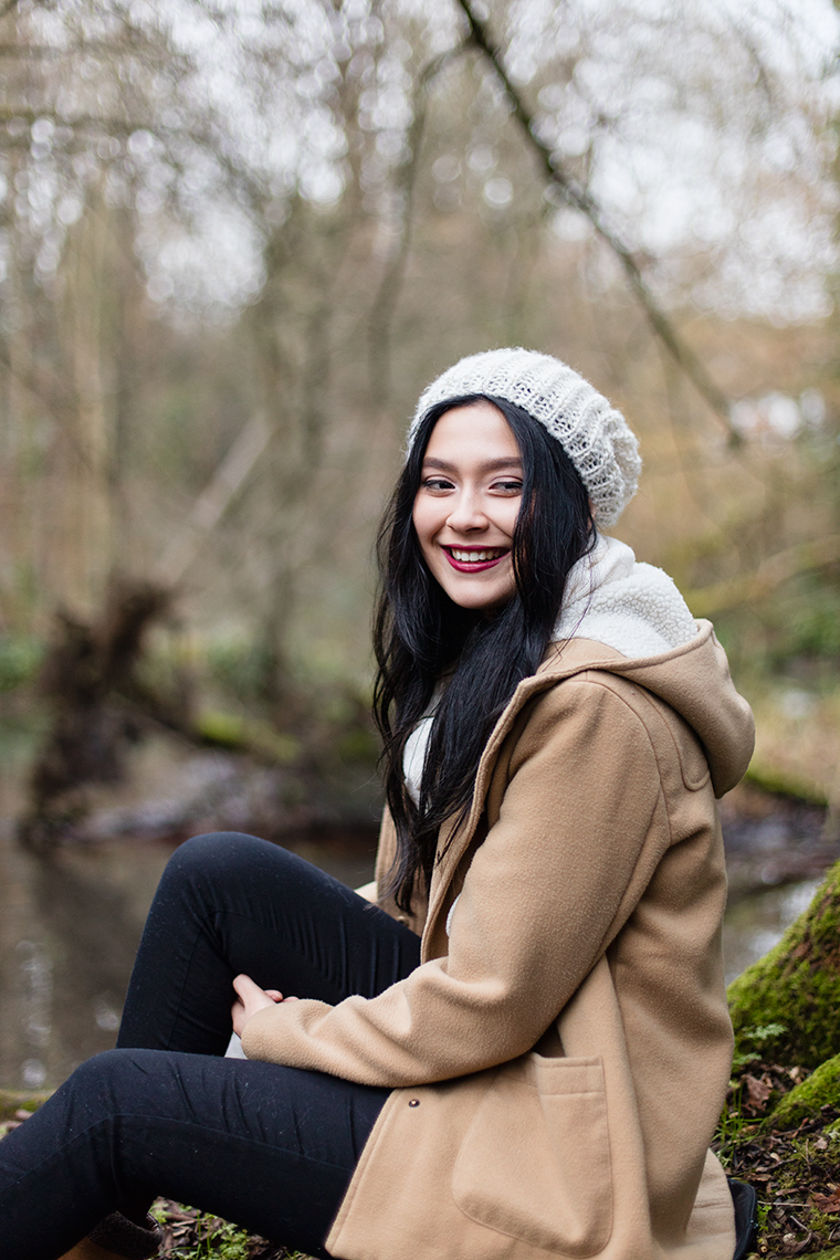 Girl with white hat and brown coat laughing and smiling