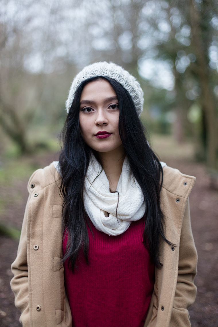 Girl with white hat and scarf, red sweater standing in the forest