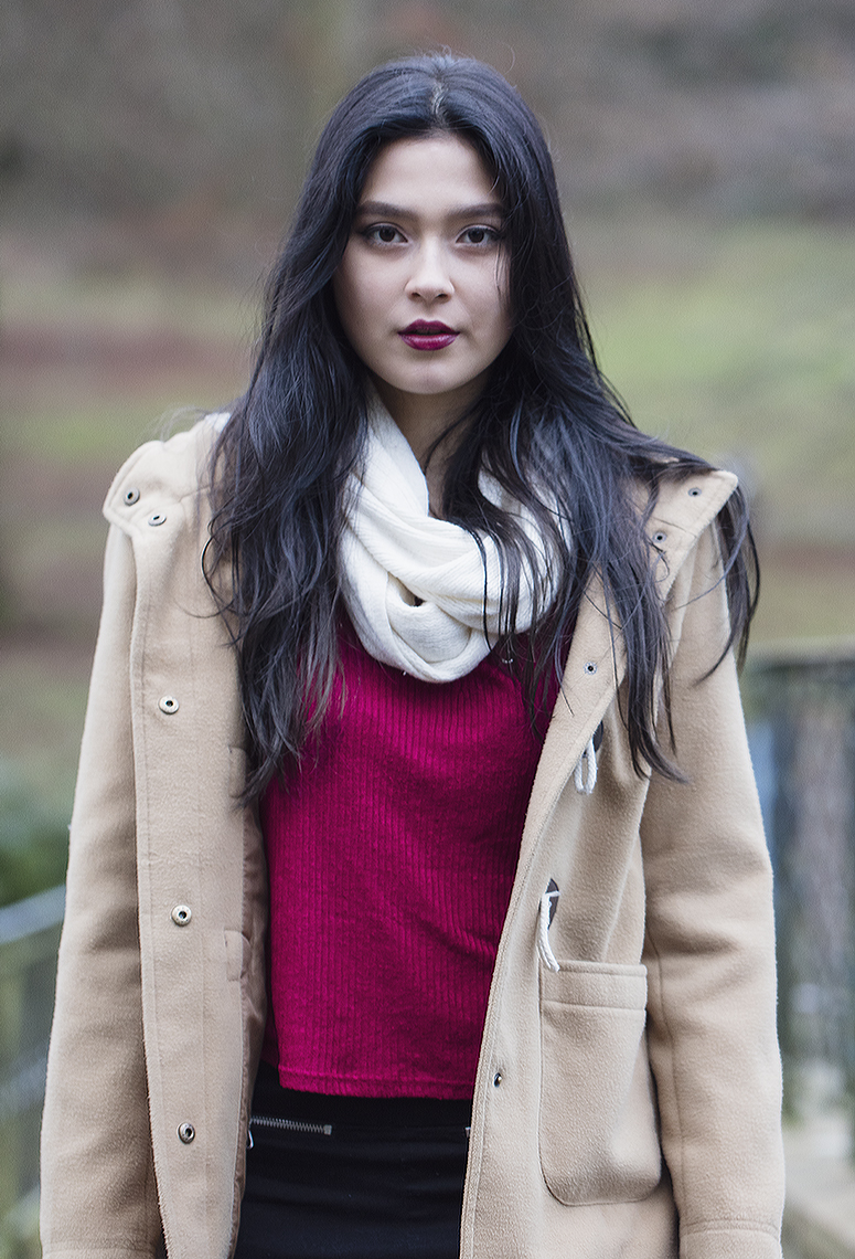 Girl in red sweater and white scarf looking into camera