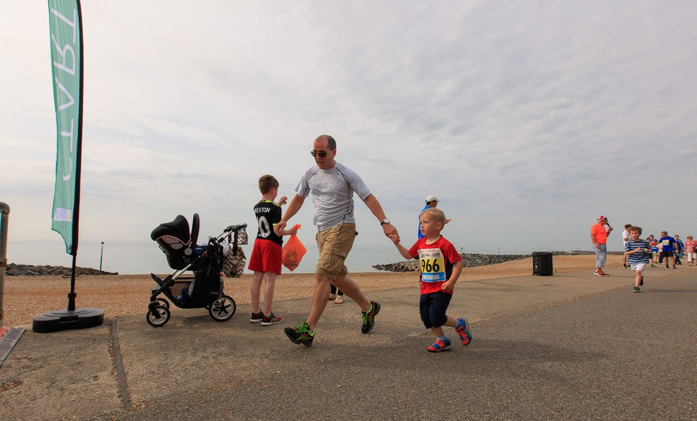 father running race aiding young son across the finish