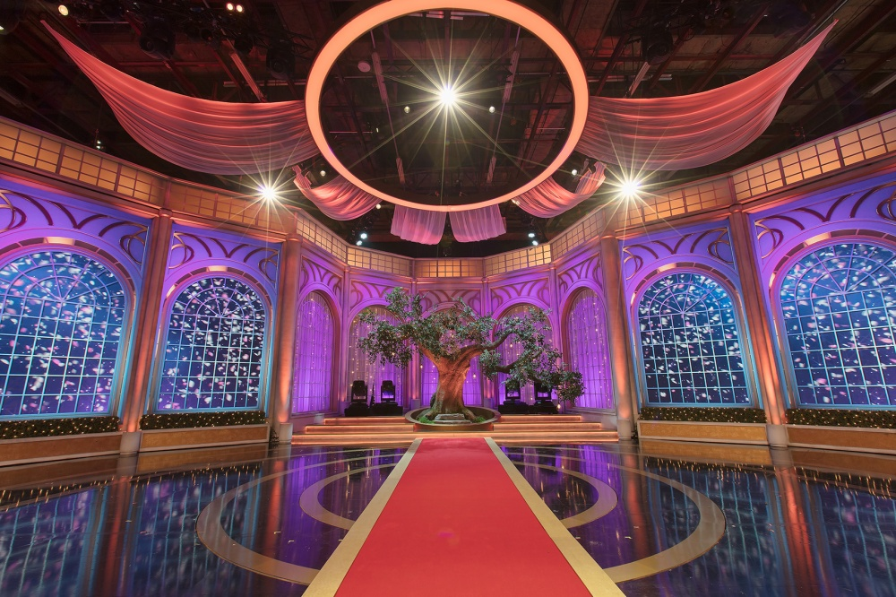 Television studio set featuring scenic pieces, a fake tree, lighting and design